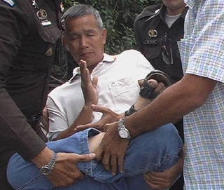 A practitioner of Falun Gong is carried away by uniformed and plain-clothes police in Bangkok. Practitioners were meditating in quiet protest across the street from the Chinese embassy.