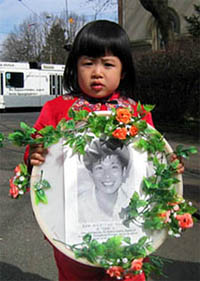 Four-year-old Fadu carries a photo of her deceased father while in a procession in Geneva during the UN Annual Human Rights meeting.