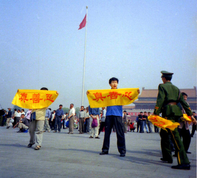 Falun Gong practitioners unfurl banners in Tiananmen Square in peaceful protest as a police officer approaches.