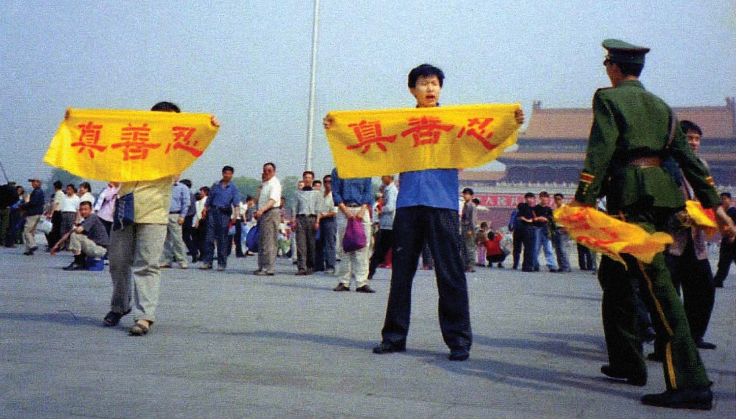 "Falun Gong practitioners raise banners reading ""Truth, Compassion, Forbearance"" as police approach on Tiananmen Square"