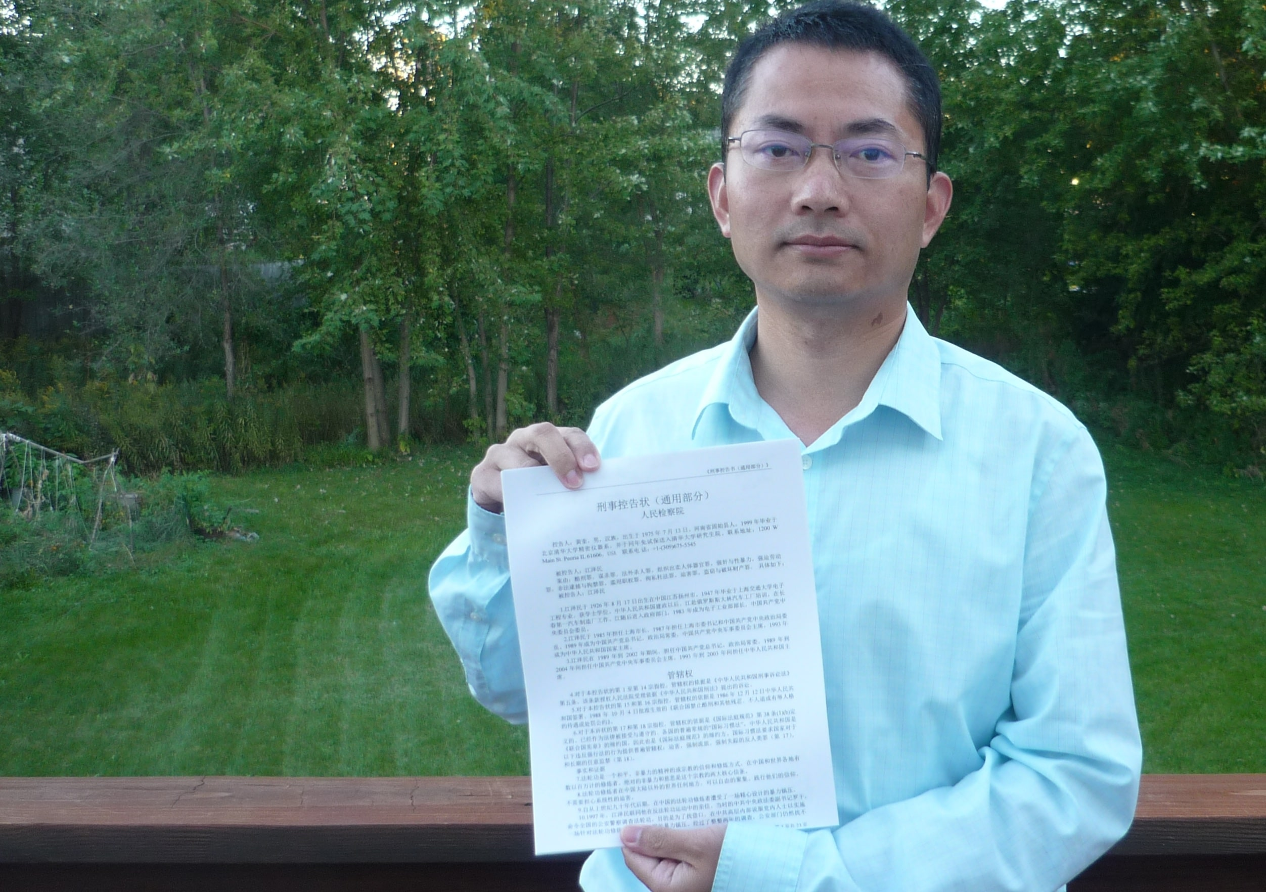 Huang Kui holds up a copy of a complaint that he submitted to Chinese courts together with 34 other people affliliated with the prestigious Tsinghua University who like him have suffered persecution for practicing Falun Gong. The complaint charges former Communist Party leader Jiang Zemin with illegal imprisonment, torture, and a dozen other crimes committed in the campaign against Falun Gong. It is one of over 160,000 such complaints submitted to Chinese courts since May.