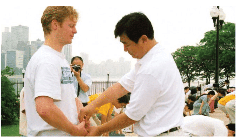 Mr. Li Hongzhi, the founder of Falun Dafa, corrects the movements of a practitioner during a group practice session in Chicago
