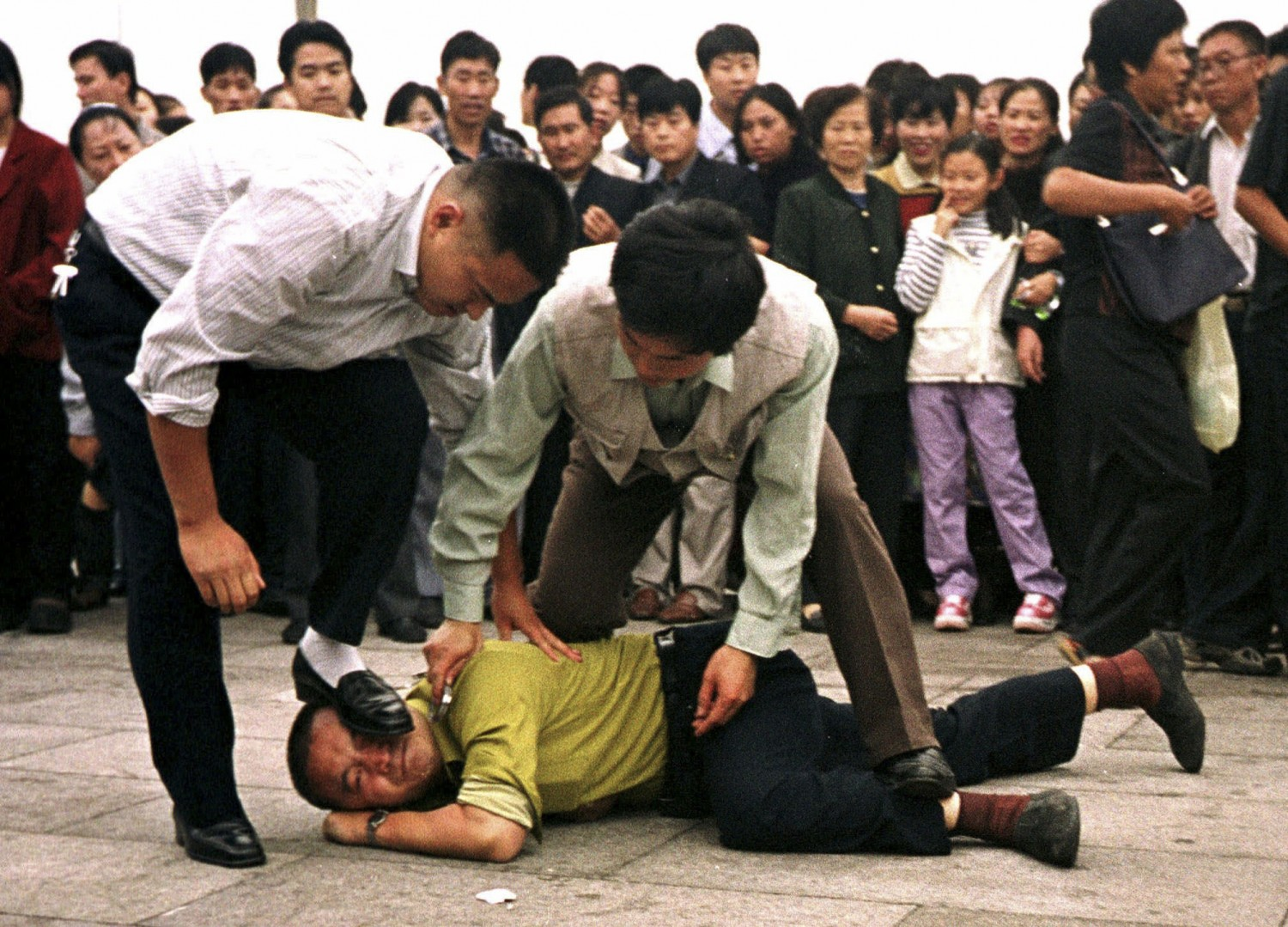 Police detain a Falun Gong practitioner who was protesting in Tiananmen Square as a crowd watches in Beijing on Oct. 1, 2000. (AP Photo/Chien-min Chung, File)