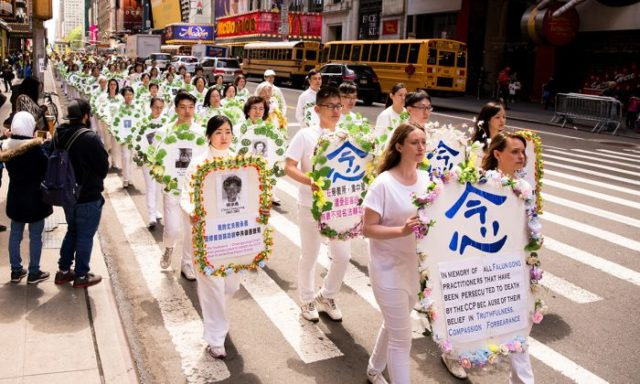Falun Gong practitioners hold wreaths with photos of people who were killed in China for their beliefs, at a parade along 42nd Street in New York City on May 12, 2017. (Samira Bouaou/The Epoch Times)