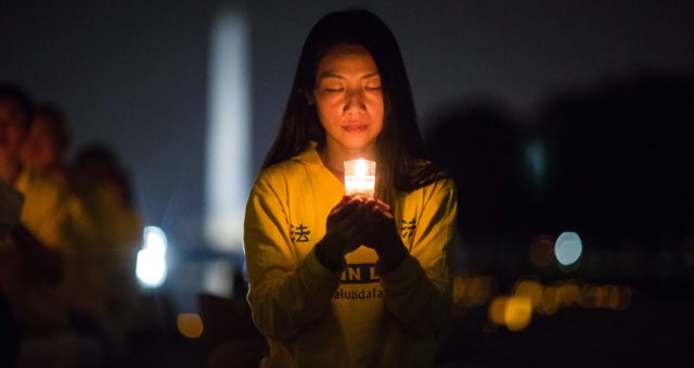 A woman joins Falun Gong practitioners holding a candlelight vigil at the Lincoln Memorial in Washington D.C., on July 20, 2017, to honor those who have died during the persecution in China that the Chinese regime started on July 20, 1999. (Benjamin Chasteen)