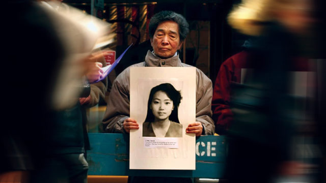 Falun Gong practitioner Kip Ng, center, holds a picture of a woman who was killed in China for her faith. (AP Photo/Gregory Bull)