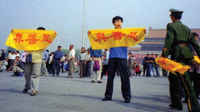 "A Chinese policeman (right) approaches Falun Gong practitioners on Tiananmen Square as they hold a banner that reads ""Truthfulness Compassion Forbearance"""