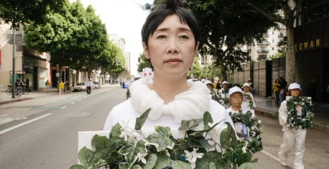 <b>Mourning Ms. Wang Yifei</b> holds a wreath to mourn her sister who was killed in a Chinese labor camp because she stood up for her faith in Falun Gong. Ms. Wang fled China to escape the same fate, and is shown here in a march in Los Angeles in 2016.