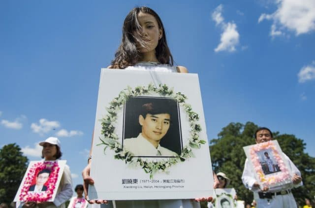 "Falun Gong demonstrators hold memorial pictures as they march on Capitol Hill in Washington, DC, July 17, 2014, as part of the events sponsored by the Falun Dafa Association of Washington, DC, to end ""Chinese persecution of Falun Gong practitioners"".       AFP PHOTO / Jim WATSON (Photo by JIM WATSON / AFP)"